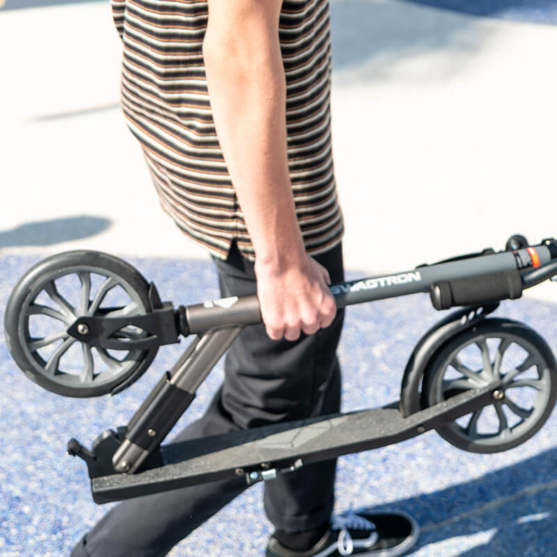 Man walking with his folded kick scooter