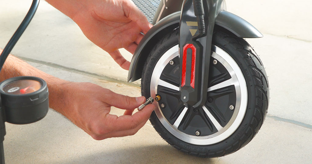 Close-up of guy using a valve extender on the front tire of a Swagger 5 Elite electric scooter.