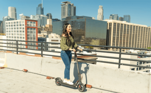Girl riding her electric commuter scooter in the city