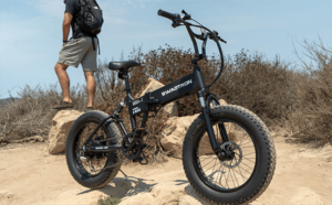Man resting after riding his electric mountain bike in an off-road trail