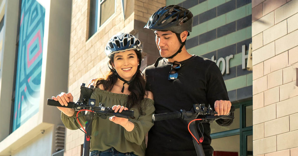Happy couple wearing their helmets on their Swagger 5 Elite to prevent electric scooter injuries