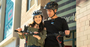 Happy couple wearing their helmets on their Swagger 5 Elite electric scooter to prevent head injuries