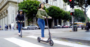 Couple crossing the street on their Swagger 5, wearing a helmet to prevent head injuries