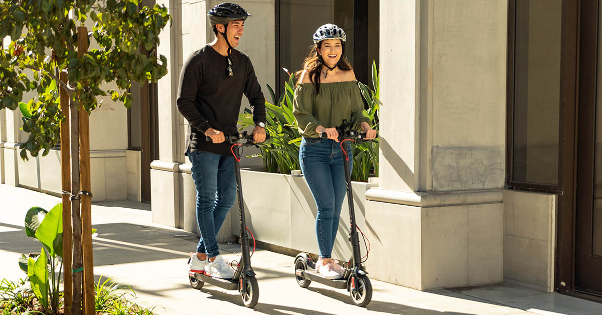 Couple riding together on their Swagger 5 Elite and wearing helmets to preventing electric scooter injuries.