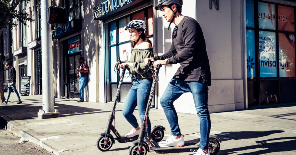 Couple wearing helmets while riding Swagger 5 Elite