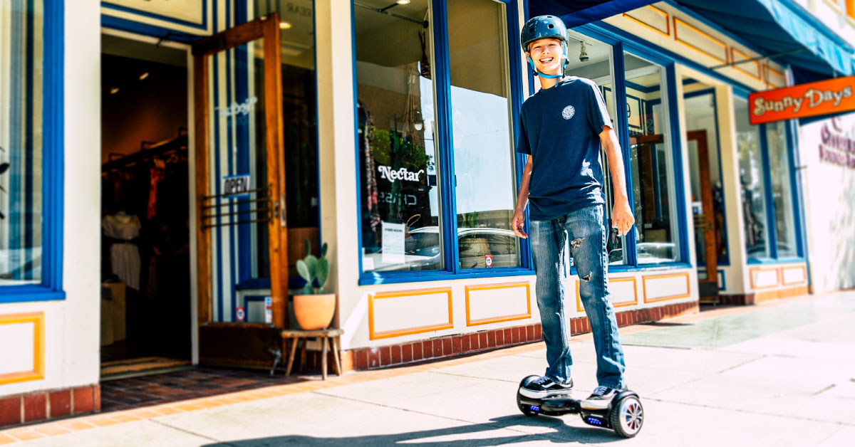Smiling kid wearing helmet and riding a Swagboard Twis hoverboard