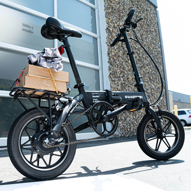 Electric Bike with rear cargo rack is parked outside of the office with boxes loaded onto the rack