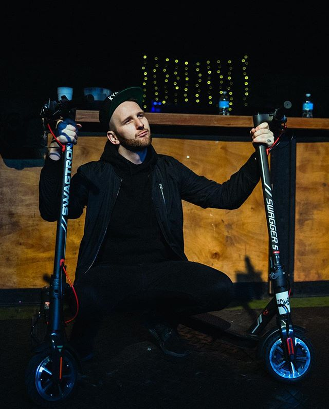 Zomboy holding two swagger 5 elite electric scooters on tour