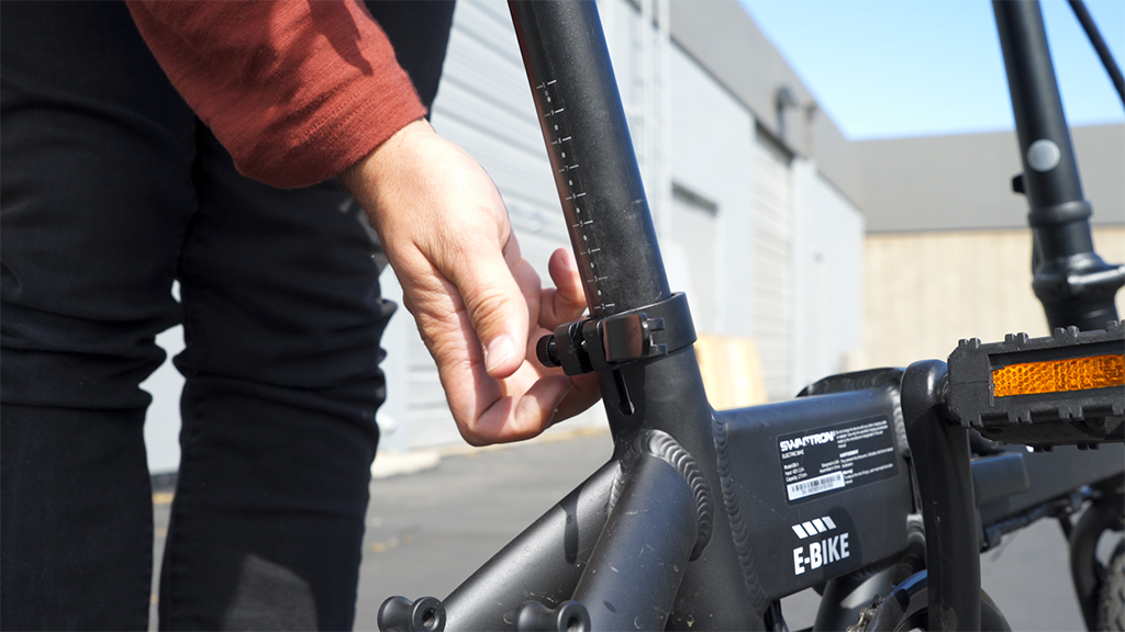 Close-up of someone tightening the seat post latch on the EB5 Pro