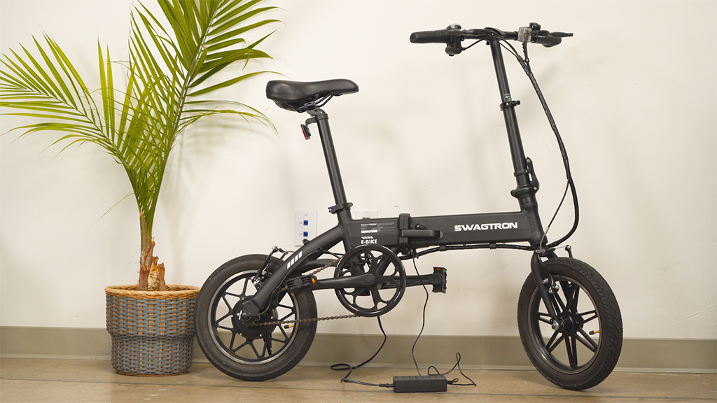The EB5 Pro electric bike, standing on its kickstand while connected to its charger
