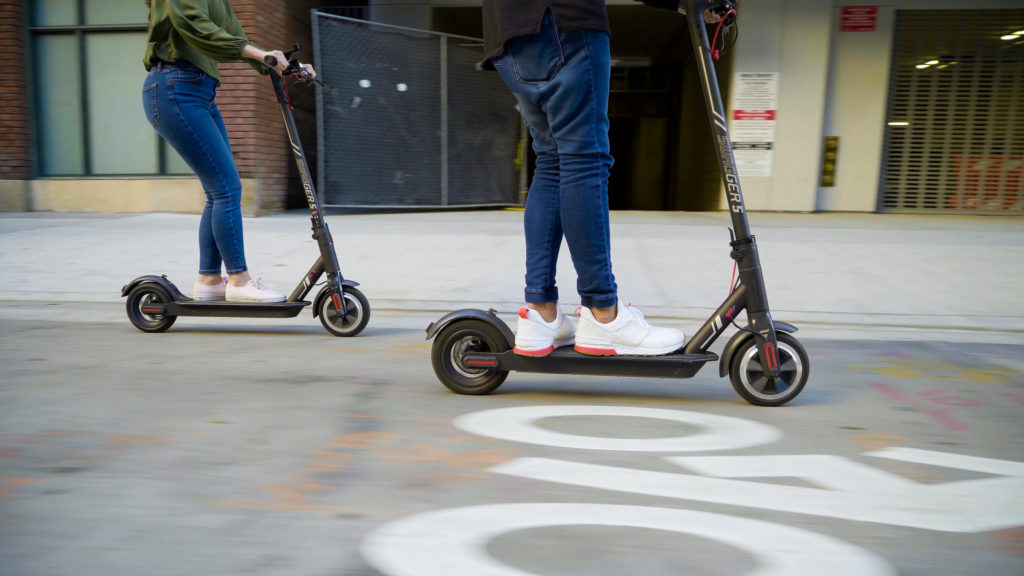 Two people riding electric SWAGTRON commuter scooters on the streets of L.A.