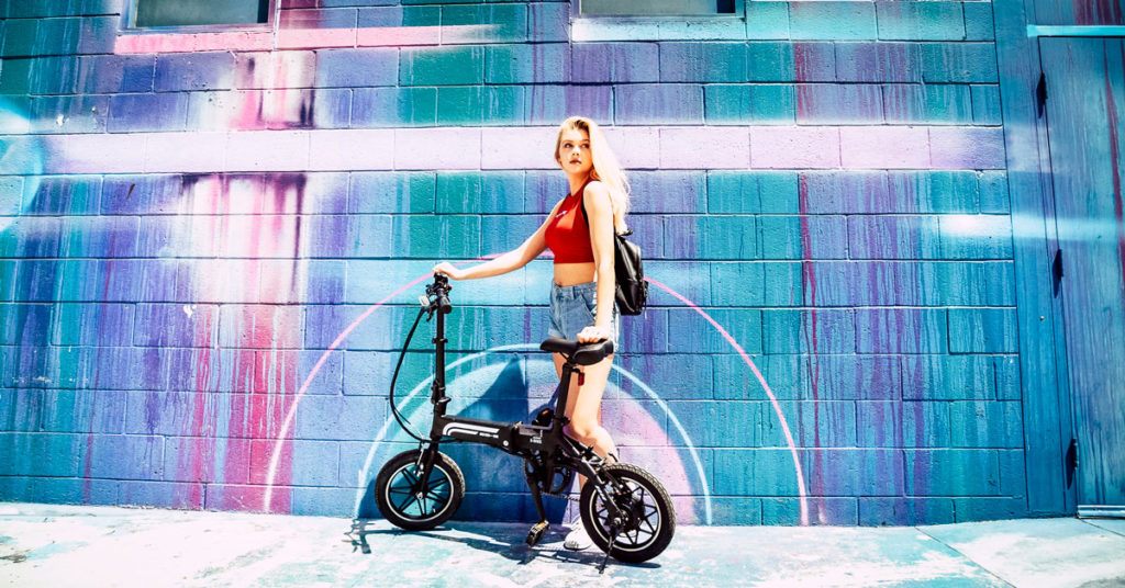 Girl sitting on her EB5 Pro eBike in front of a colorful mural.