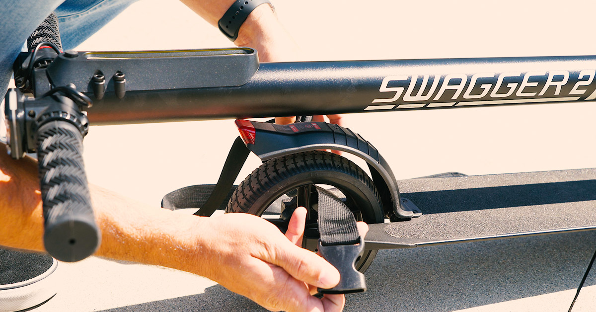 Close-up of guy looping the Swagstrap through the rear wheel of the Swagger 2 Classic