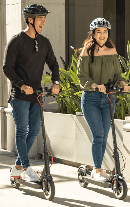 Couple riding their Electric Scooters while traveling around the city