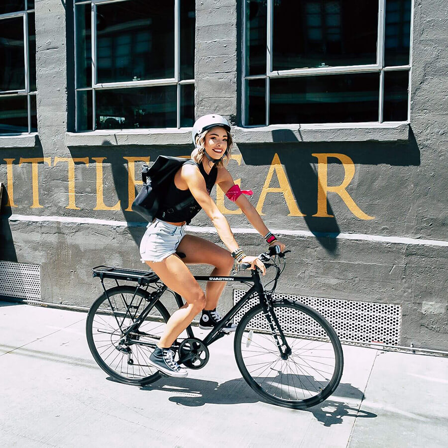 Girl working as a messenger in the city delivers her packages on the SWAGTRON EB12 eBike