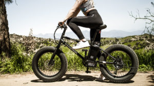 Close-up of fit woman riding EB6 fat-tire off-road electric bike on gravel road.
