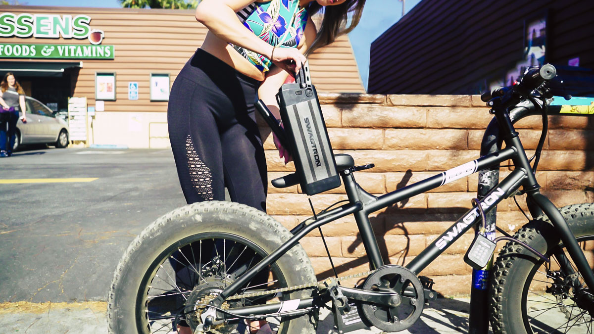 Fit woman removing swappable battery from the EB6 eBike