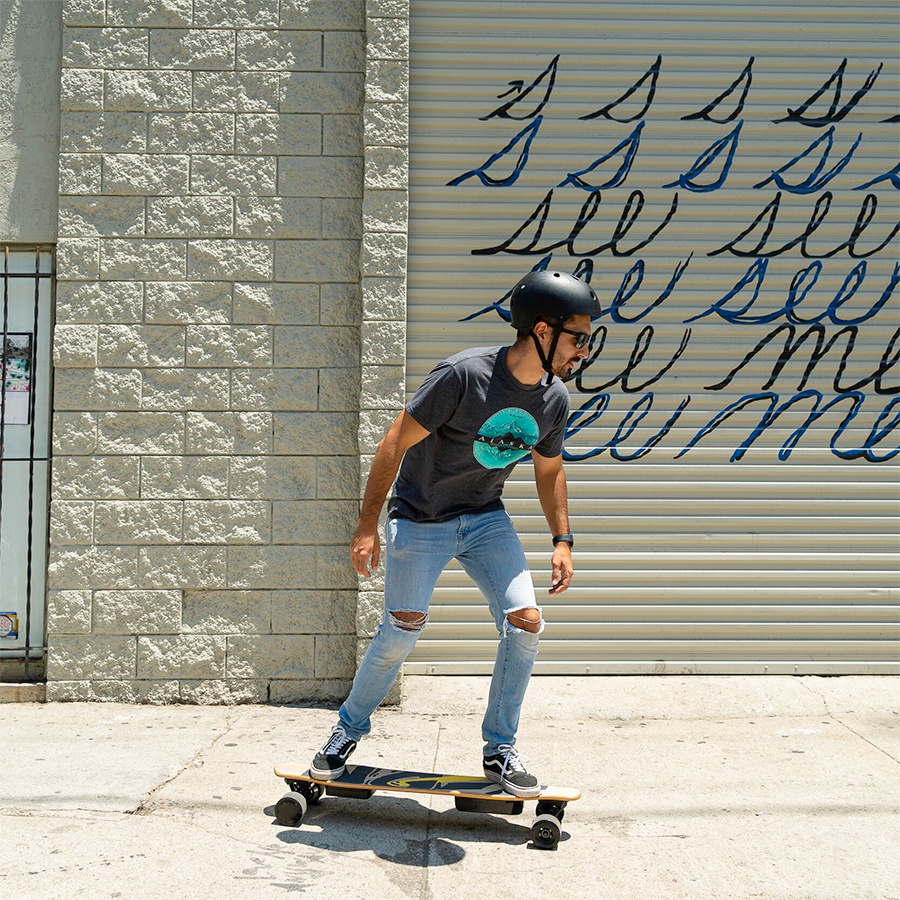 Young man riding his NG2 Electric Longboard powered by control remote