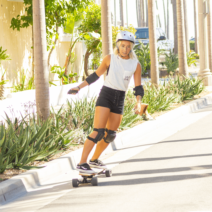Young lady riding her NG2 electric longboard in the street on her way to the store.