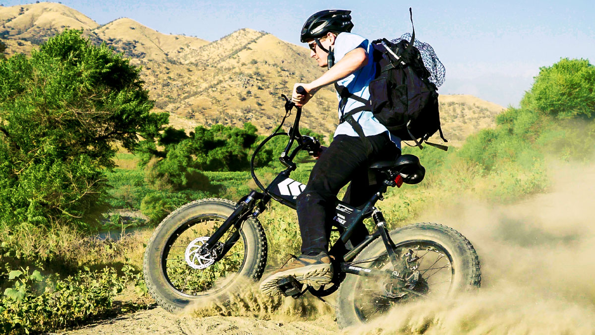 Man wearing helmet riding uphill, off-road on his EB8