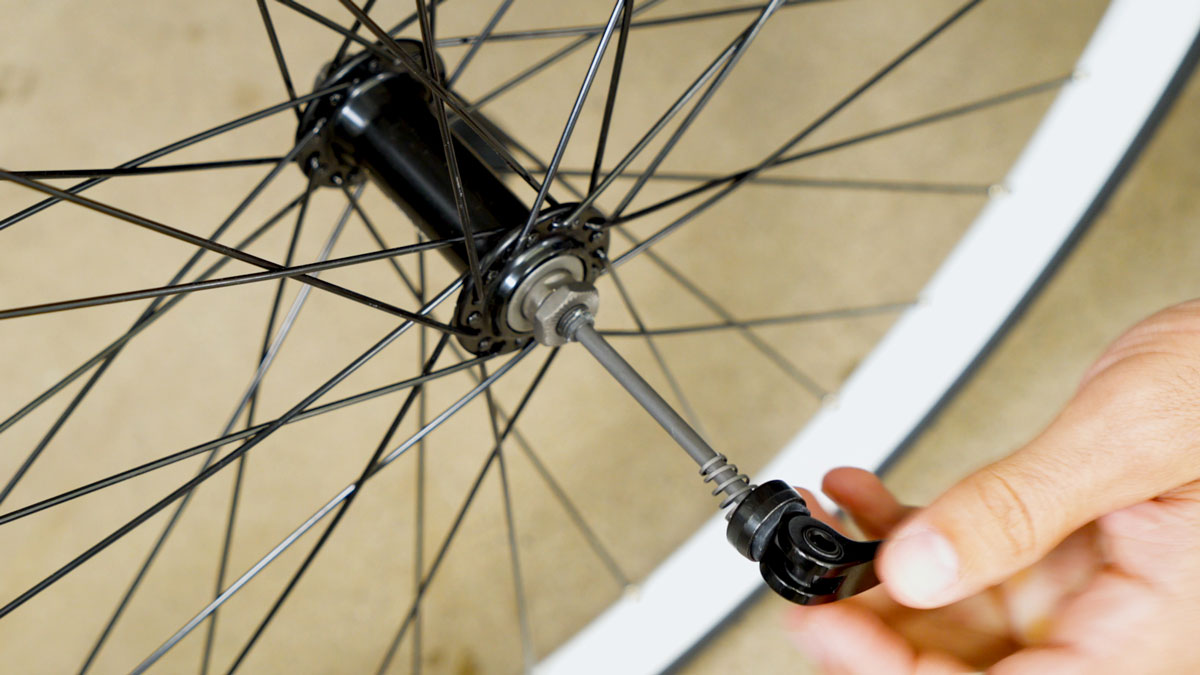 Close up of man inserting the quick-release skewer through the center axle of the front wheel