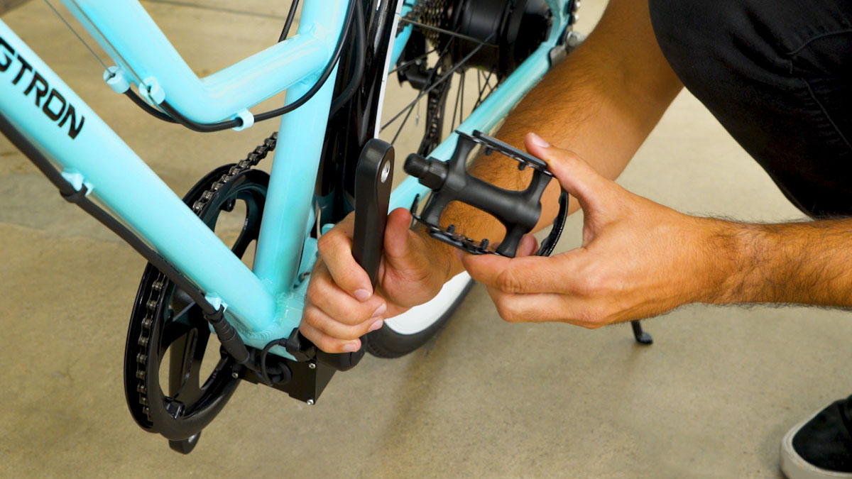 Close up of man attaching a pedal onto the crank arm of the EB9 eBike