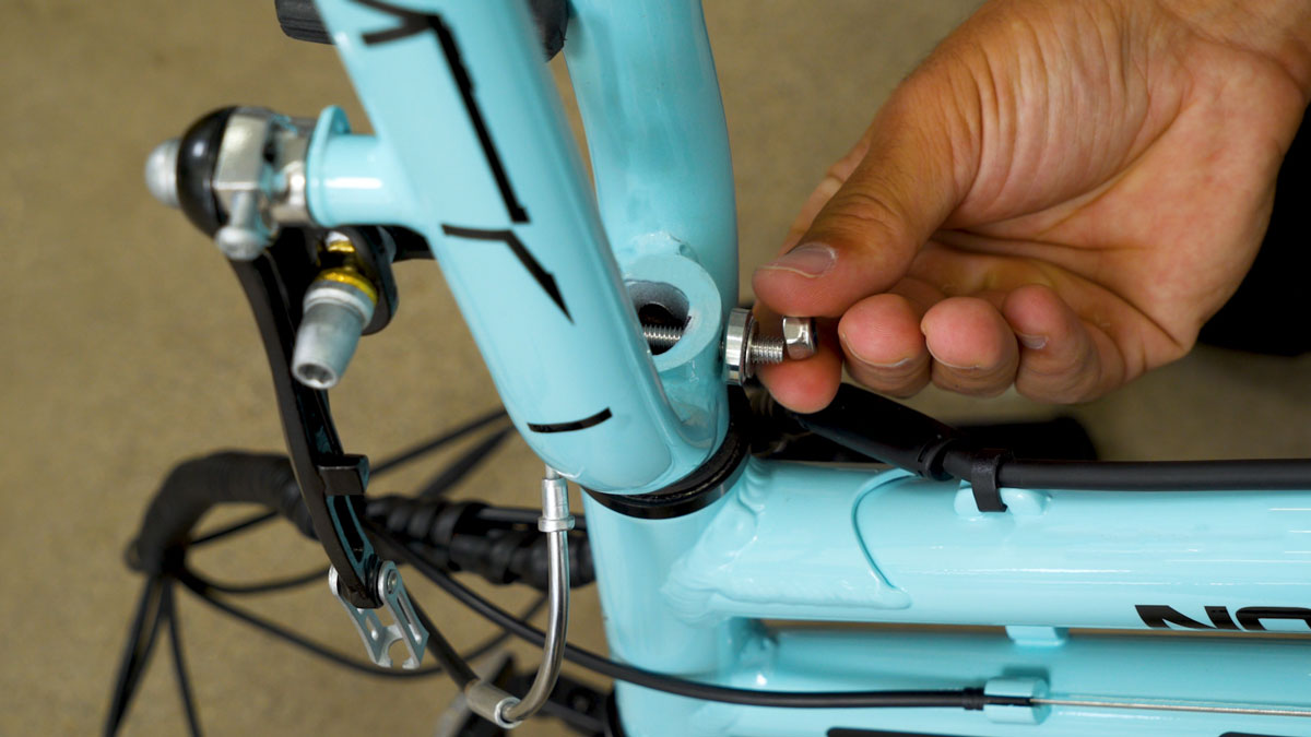 Close up of man removing the nuts and bolts from the front fork to attach the fender.
