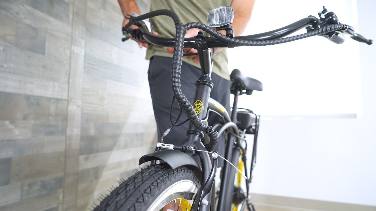 Close-up of man adjusting the handlebar alignment on the EB11 (line it up with the front wheel)