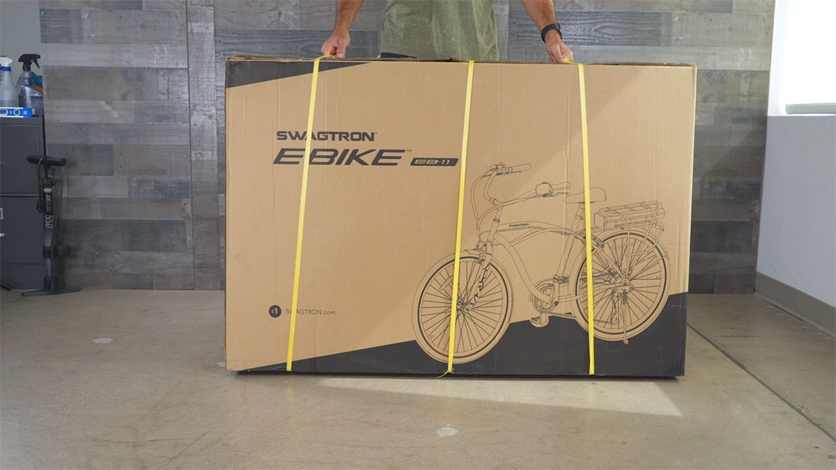 Close-up of man inspecting the package his EB11 came in for any shipping or carrier damage
