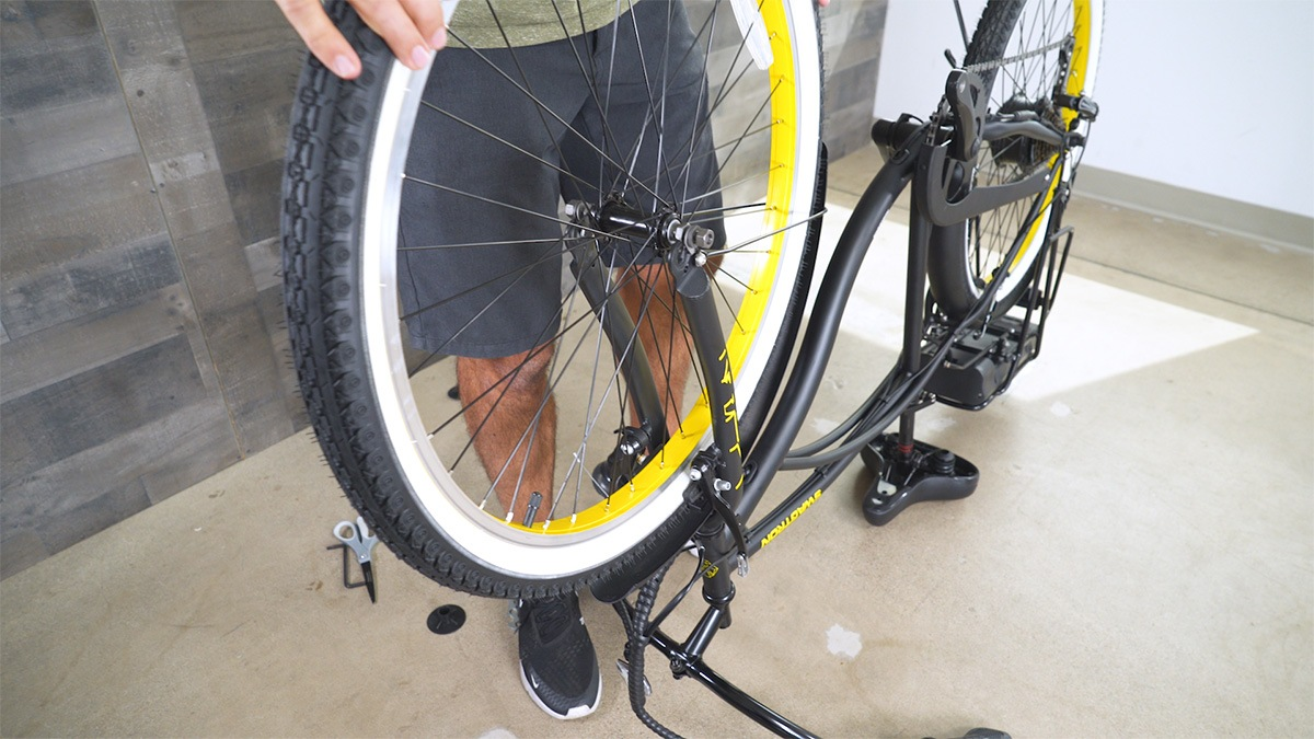 Close-up of man installing the front wheel of the EB11