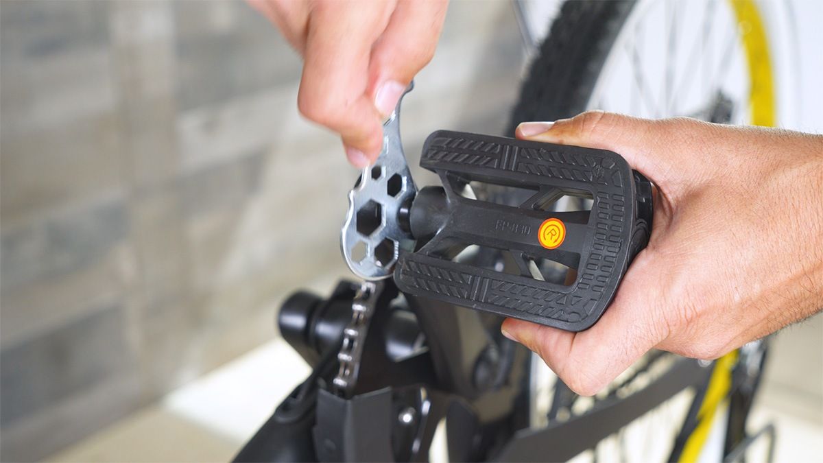 Close-up of man using the bike wrench to attach one of the pedals on the EB11