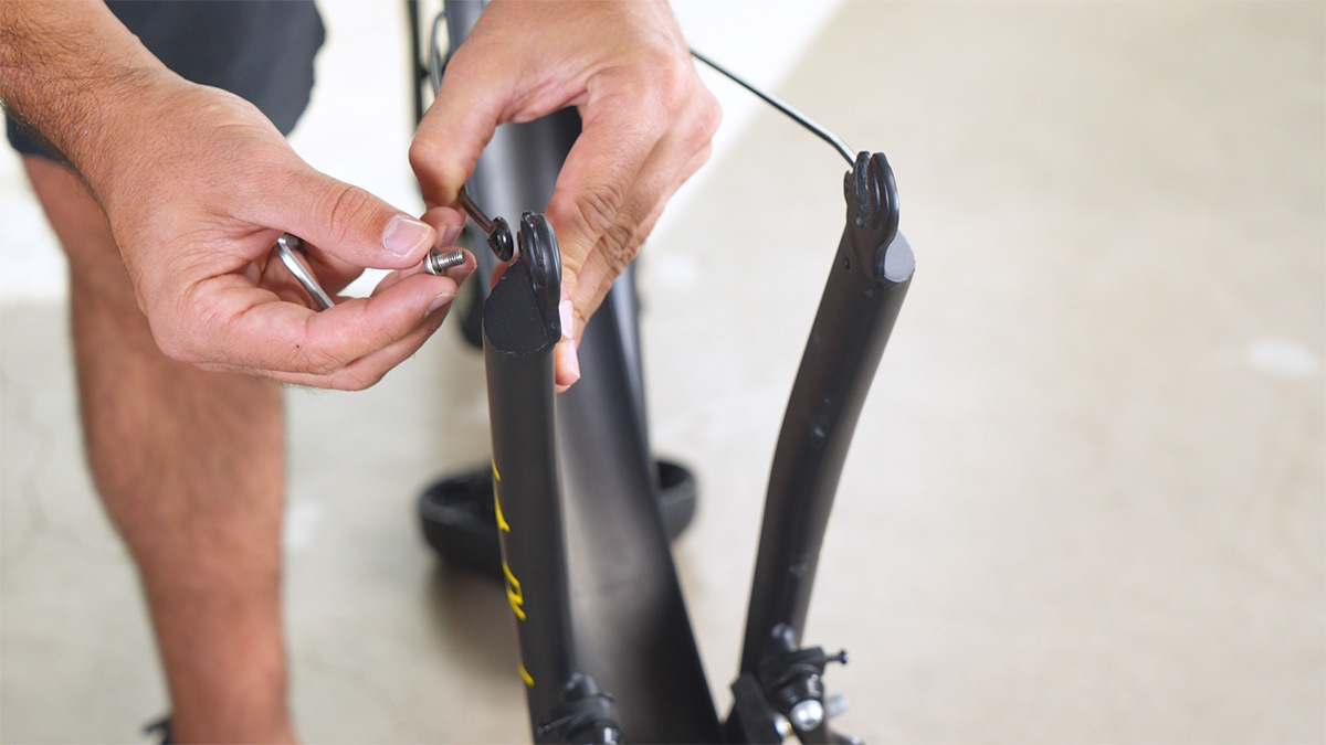 Close-up of man reattaching the lower fender stays on the EB11 after installing the front fender