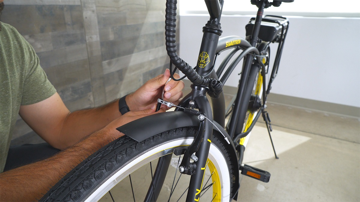 Close-up of man reconnecting the front brakes after assembling the EB11's fender