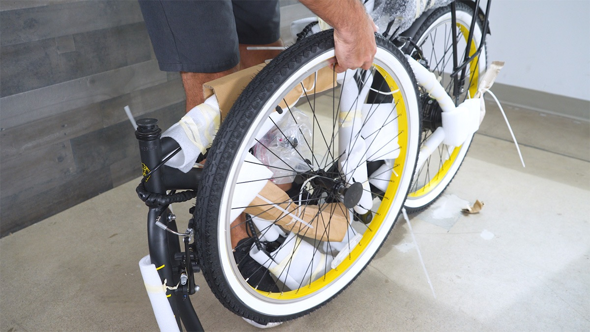 Close-up of man removing the front wheel from the packaging