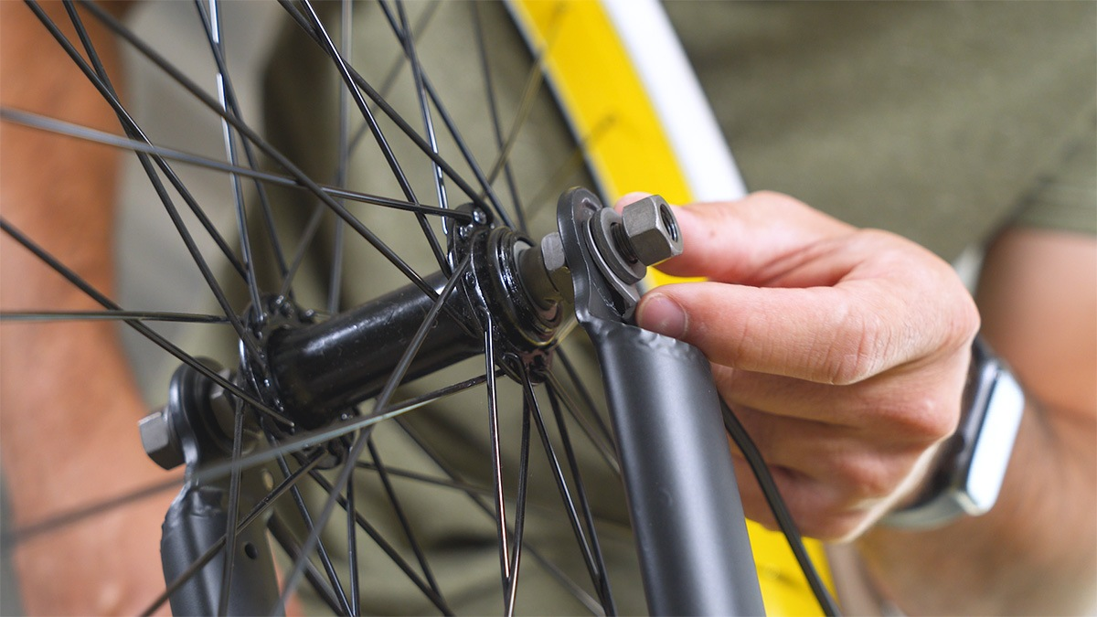 Close-up of man setting the retainer clip on the EB11's front wheel for support