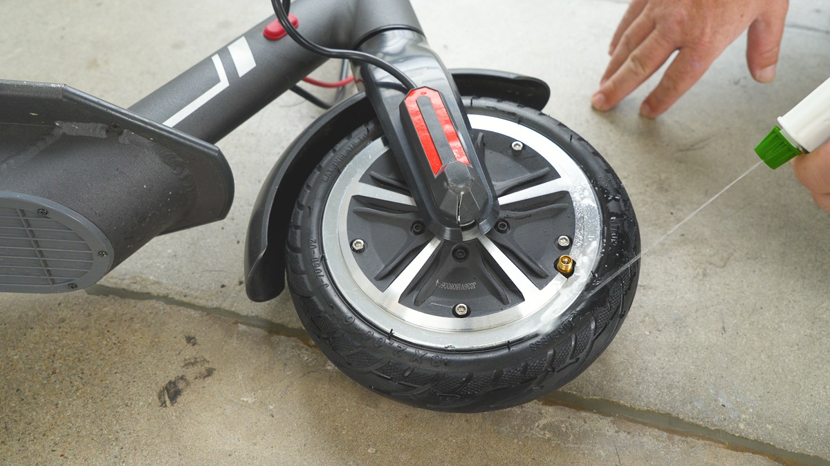 Close-up of guy spraying the tire with water to check for air leaks