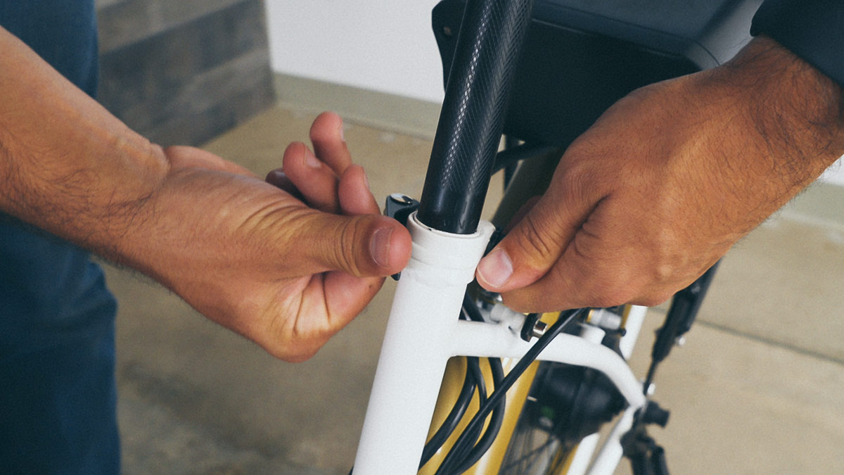 Close-up of man tightening the seat post by hand.