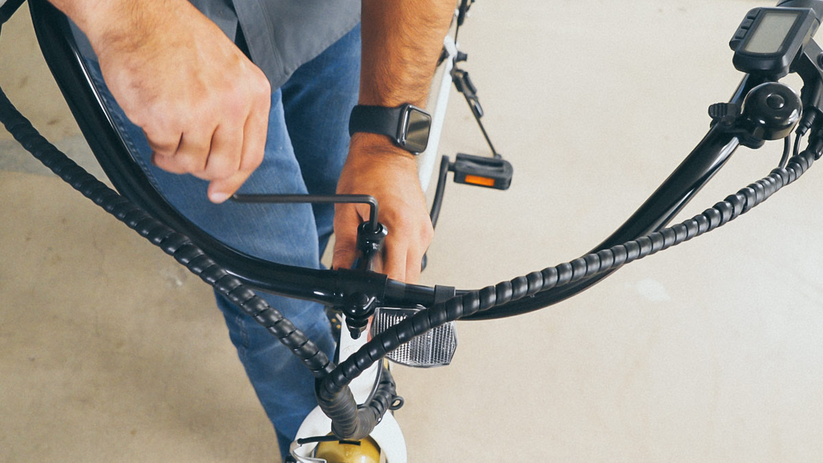 Close-up of man tightening the handlebar with the hex key after aligning it with the front wheel.