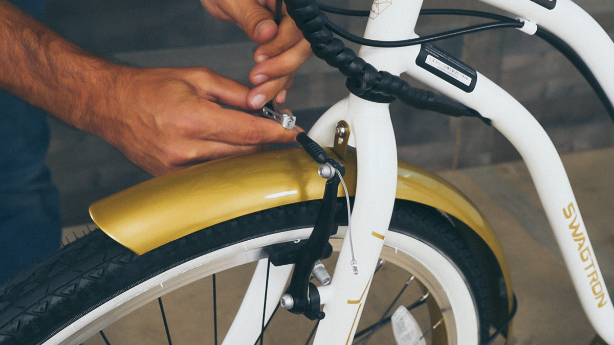 Close-up of man reconnecting the front brakes.