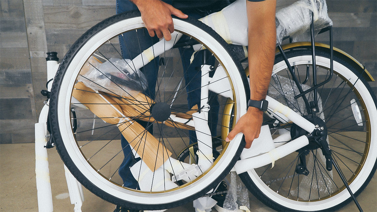 Close-up of man removing front wheel from packaging.