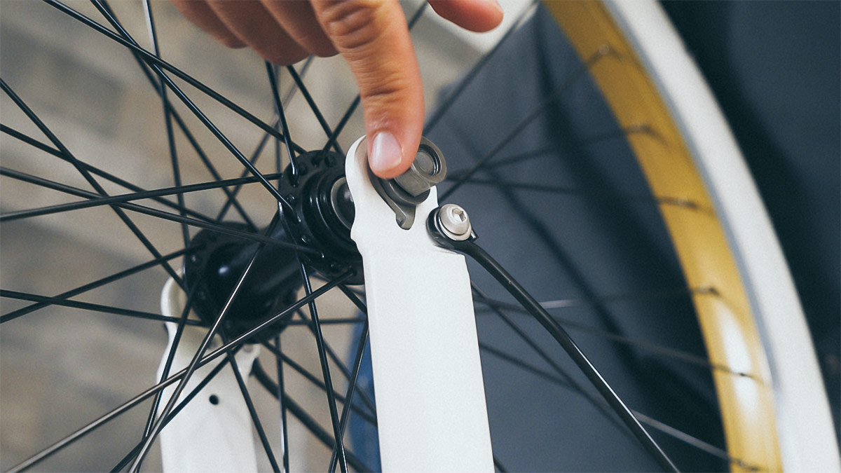 Close-up of man setting the retainer clip in the front wheel of the EB10.