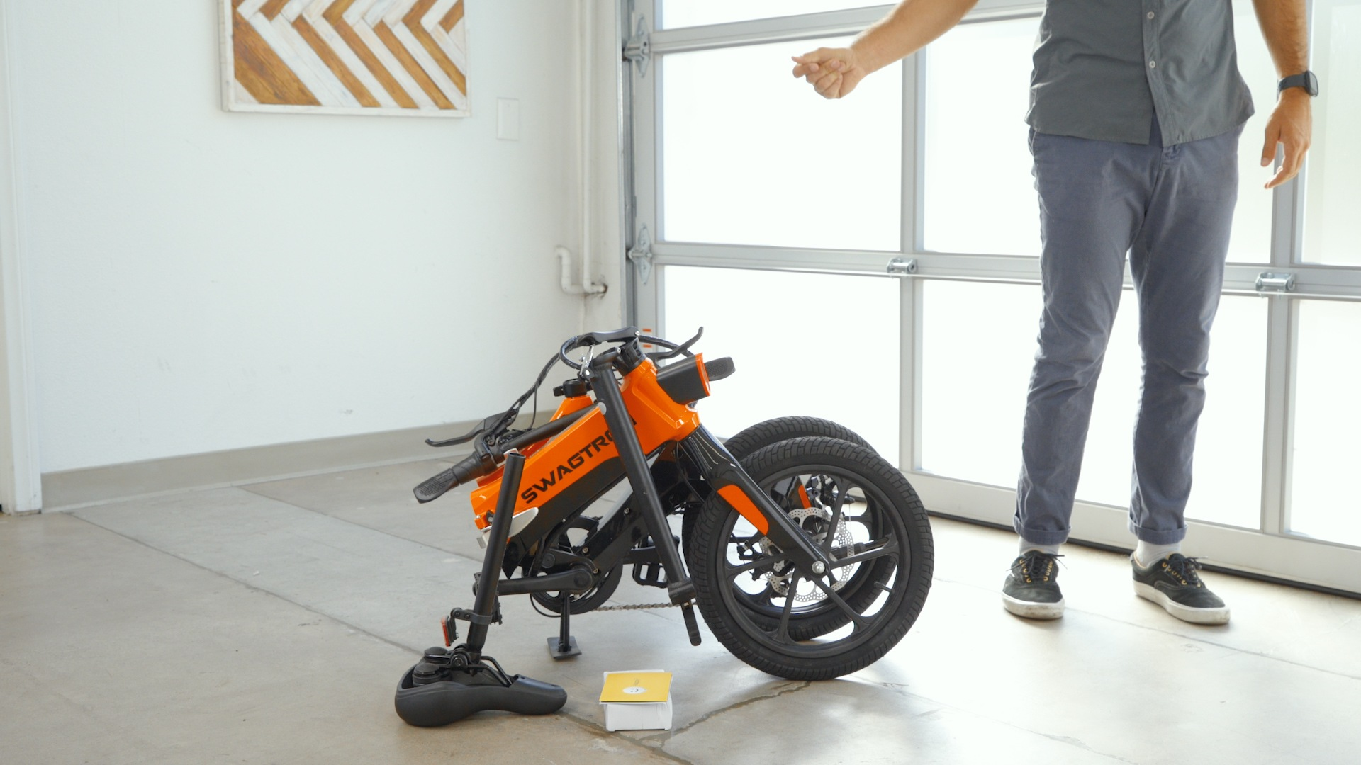 Man standing next to a folded EB7 Plus eBike after removing it from packaging.