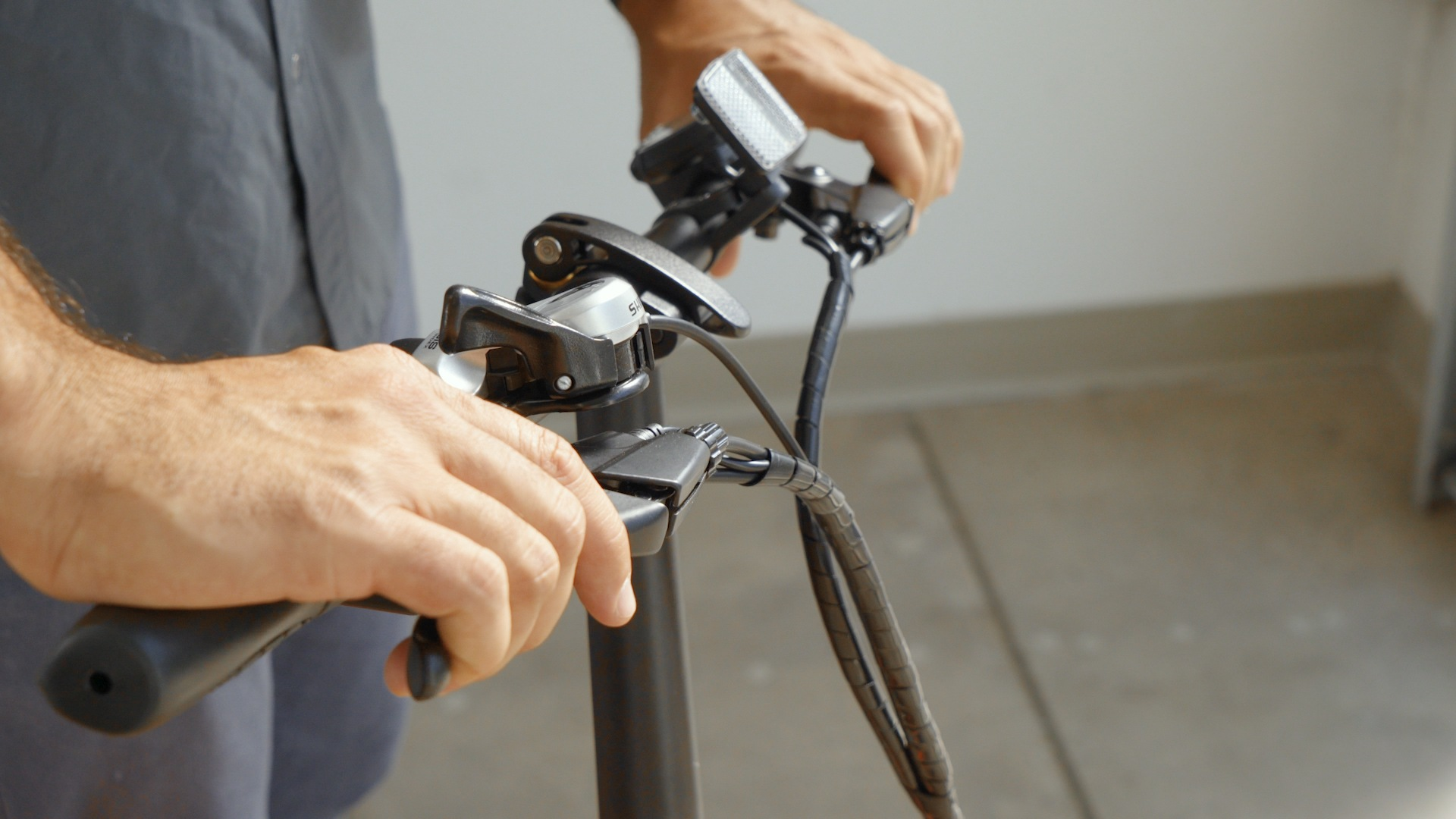 Closeup of man squeezing the hand-brakes on the handlebar.