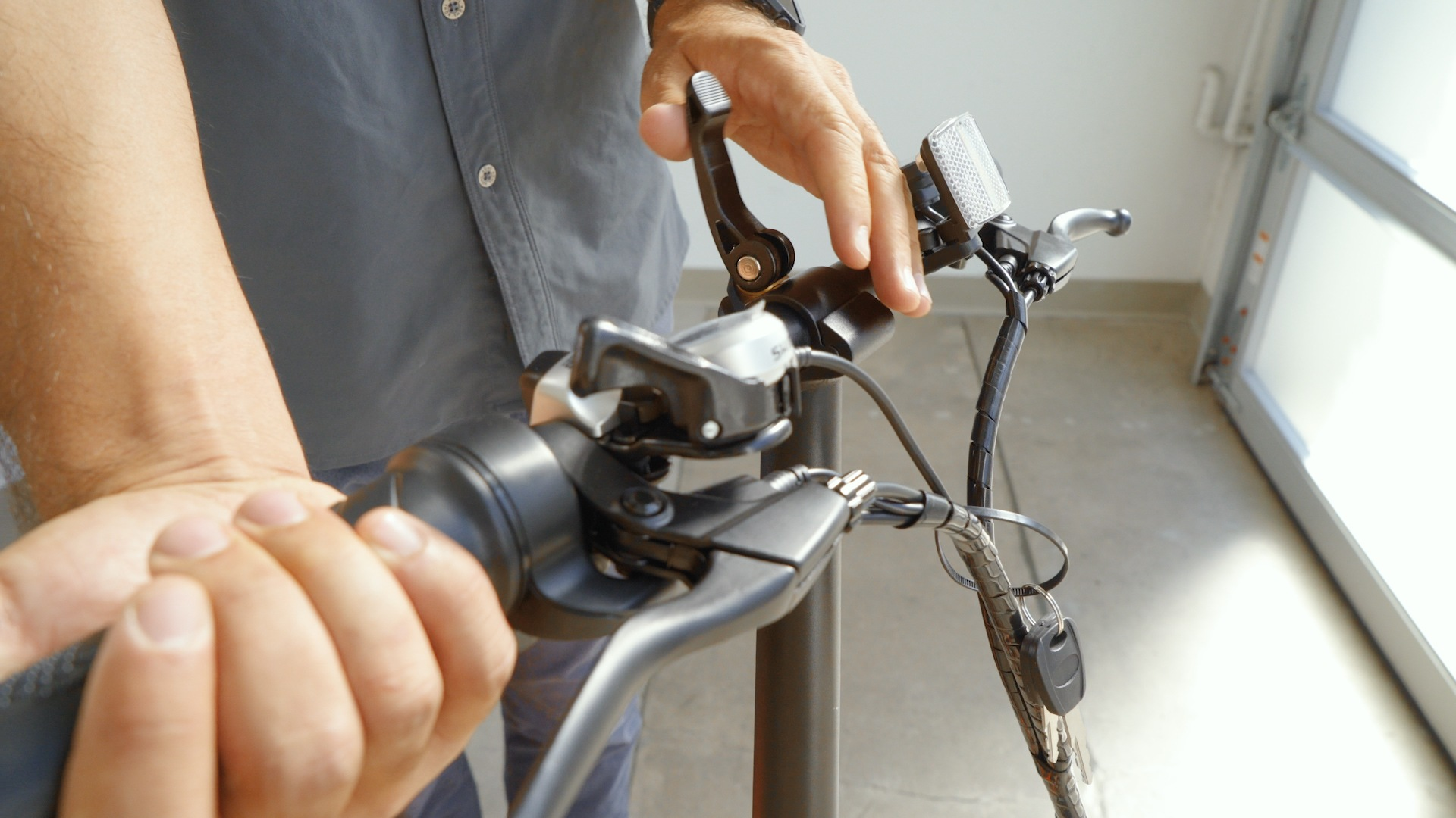 Closeup of man closing the latch on the handlebar after re-adjusting it.