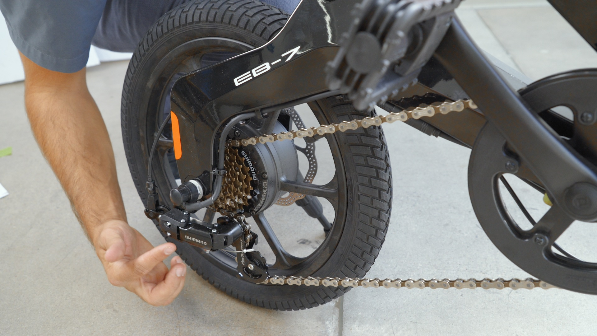 Closeup of man pointing to the rear wheel of the EB7 Plus with its brakes and Shimano gears.