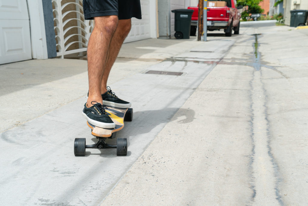 Closeup of man riding the NG2 electric longboard on pavement.