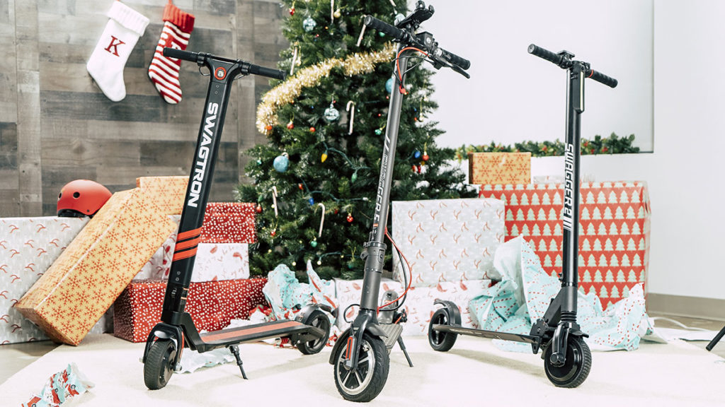 SWAGTRON electric scooters with christmas bows in front of a Christmas tree.