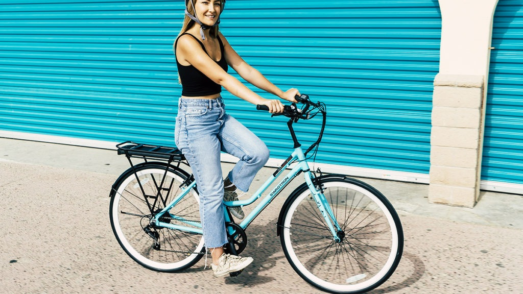 Woman wearing helmet and sitting on an EB9 step-through electric bike from SWAGTRON.