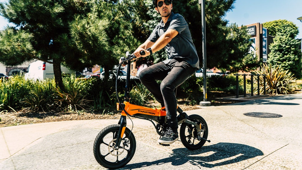 Man wearing sunglasses and a helmet, riding an EB7 electric bike