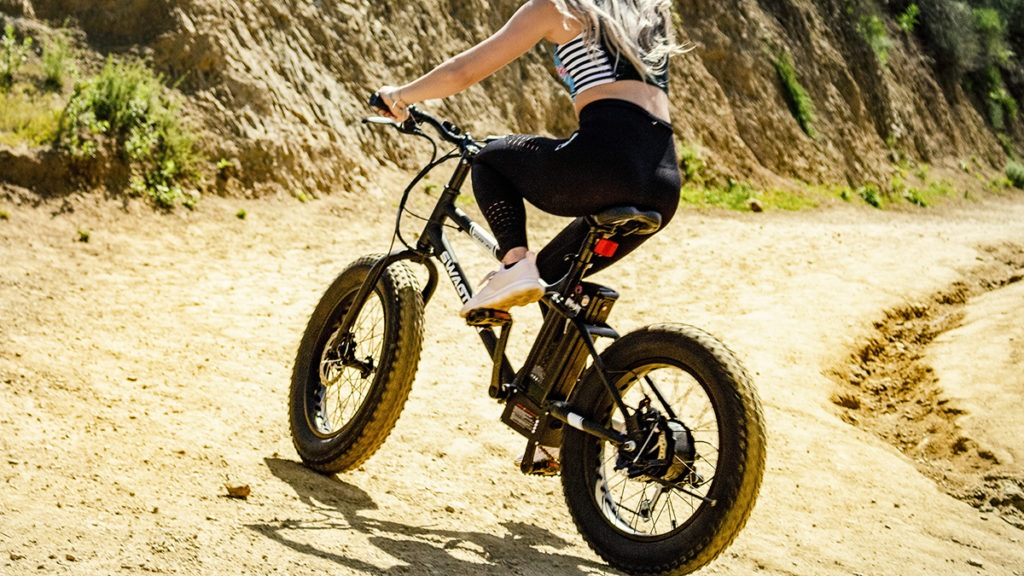 Rear view of young woman trail-riding with her EB6 fat-tire electric bike